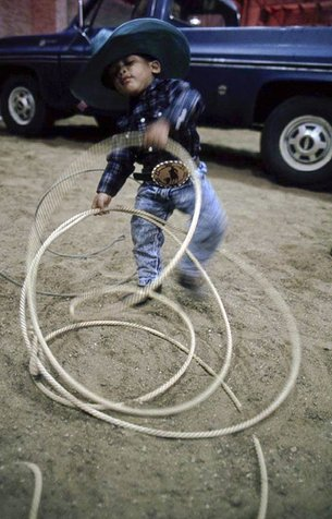 A four-year-old plays with his fathers rope during a rodeo in Dallas.