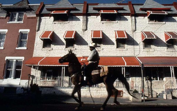 Bob Hill rides his horse down a street of rowhomes in North Philadelphia