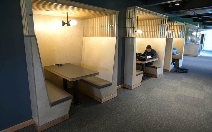Student studies at table inside dorm lobby
