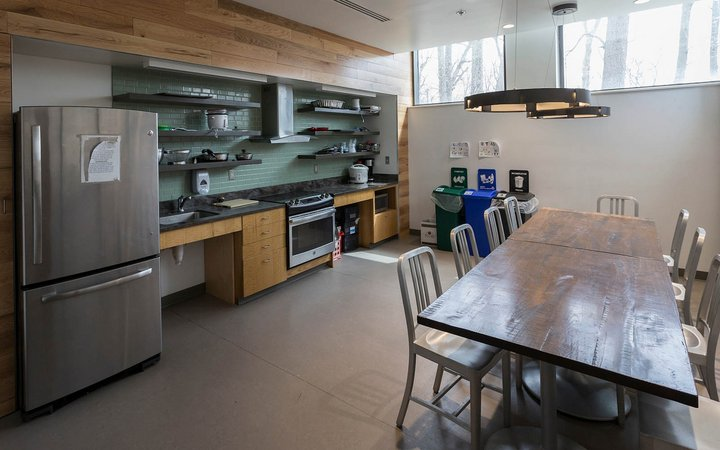 Kitchen space with table, fridge, pots and pans