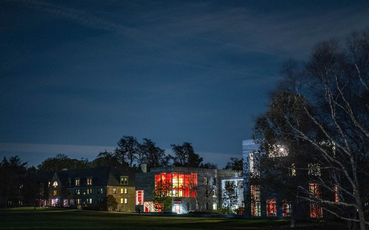 Exterior shot of dorm building at night, illuminated from within.