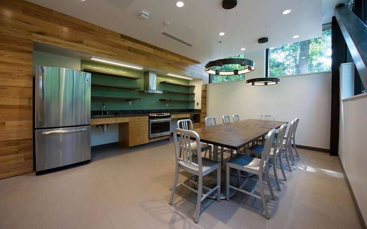 Kitchen space with table in the middle of the room and large metal fridge to the left.