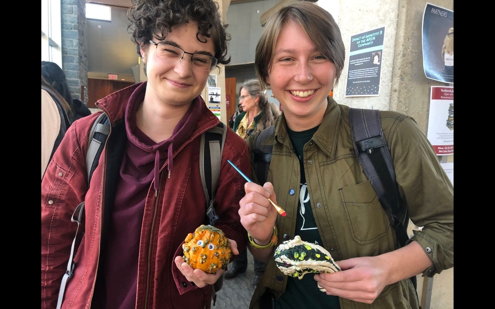 Two smiling students standing side by side holding painted clay items and a paintbrush