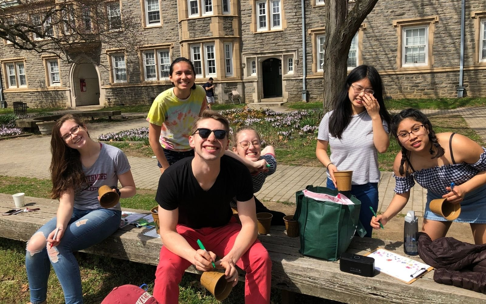 A group of students hanging out in a dorm courtyard on a sunny day make faces at the camera