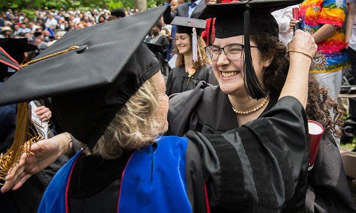 graduate hugging faculty member