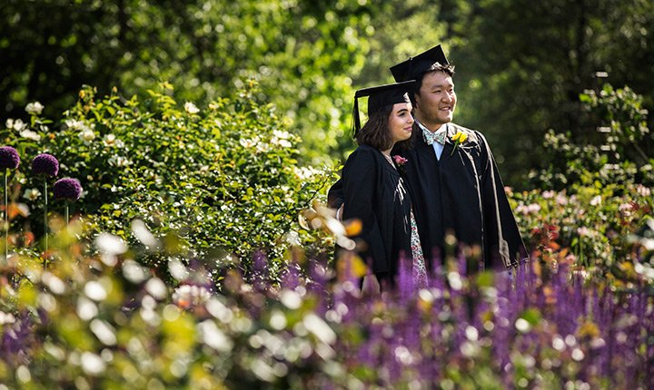 students posing amidst flowers