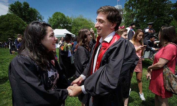 Two graduates holding hands