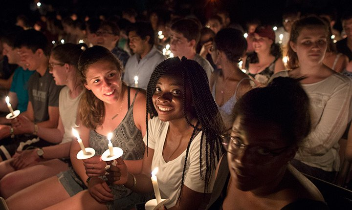 Students sit with their candles