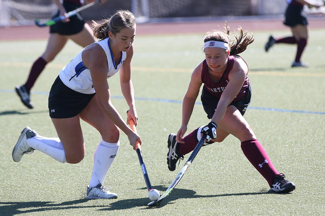 Field hockey player fights for ball