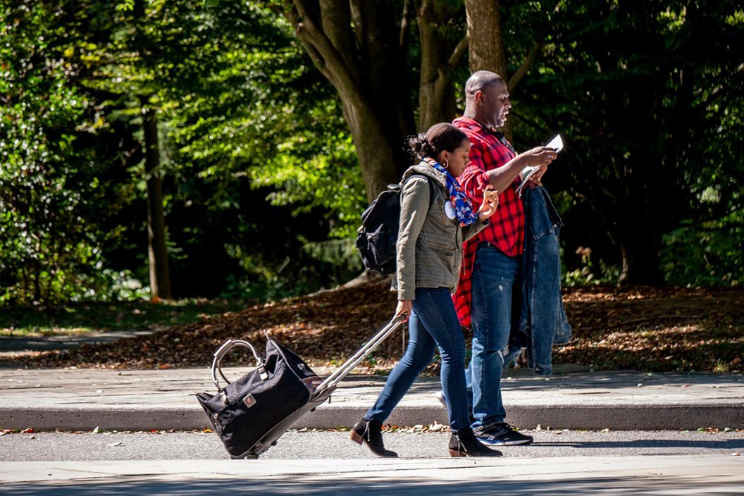 People with suitcases walk on Swarthmore's campus
