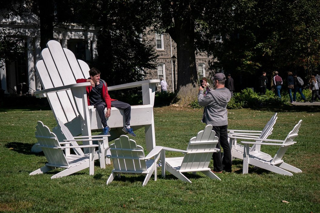 Student takes photo on Adirondack chairs
