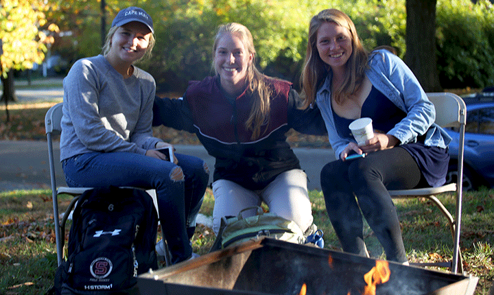 Students pose for a photo by the fire pit