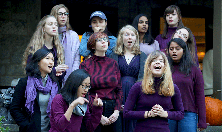 A group of students stand together singing