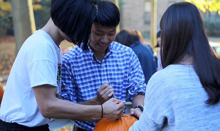 Students work together on carving a pumpkin