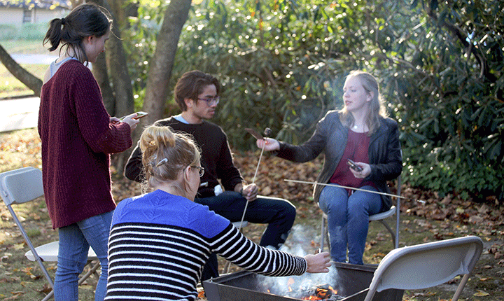 Students make smores around a fire
