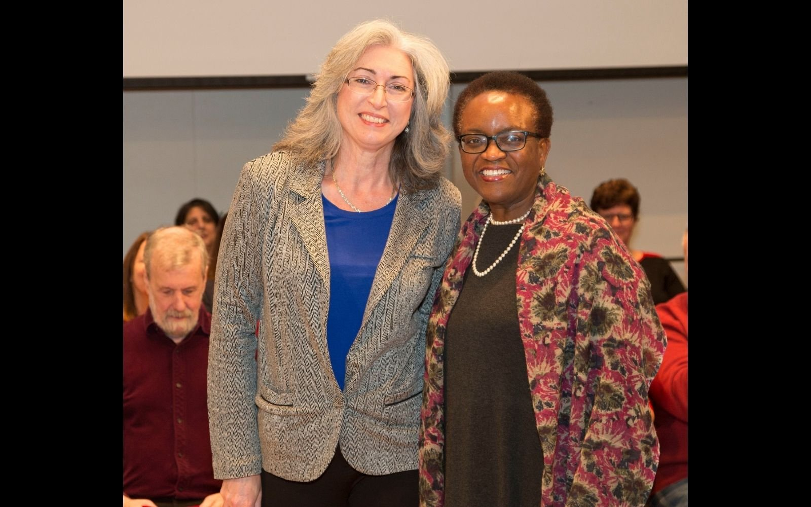 Two woman stand beside each other, smiling at the camera. The woman on the left wears glasses, a grey jacket, and a bright blue top and has shoulder length white hair. The woman on the right has close cropped hair and wears glasses and a long patterned jacket.