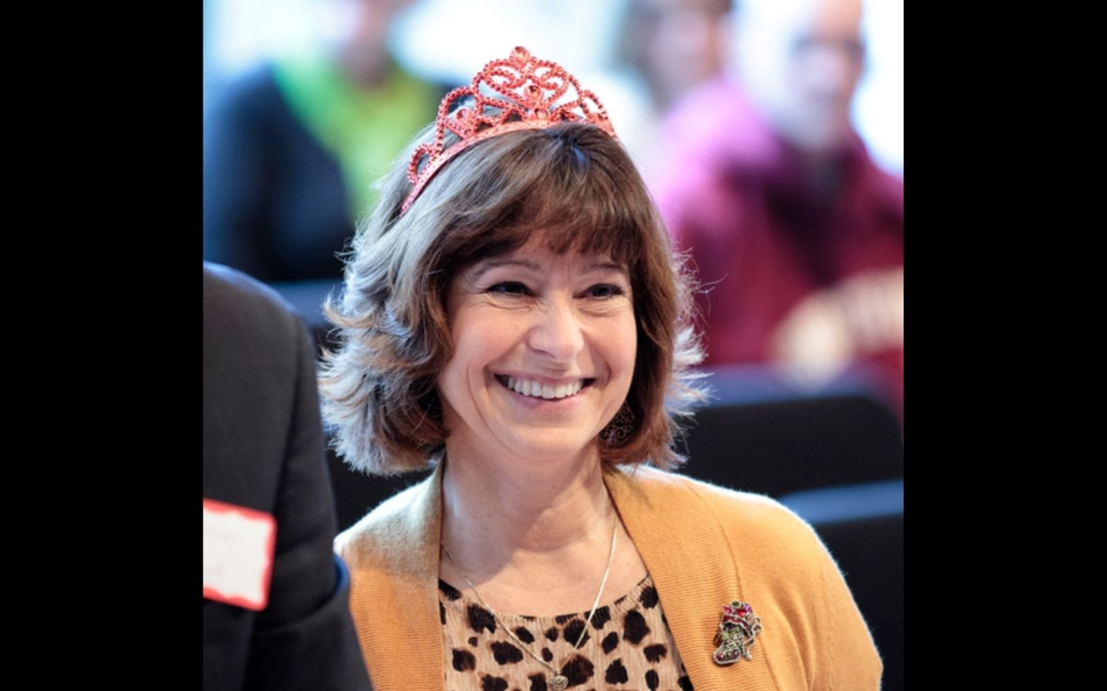 A woman with brown hair and bangs wearing a yellow cardigan and pink toy tiara smiles widely.