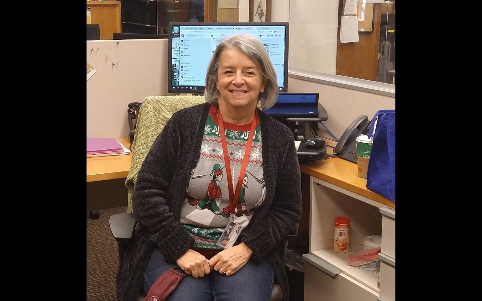 Woman with short grey hair wearing a long black cardigan and red lanyard sits at a desk with a computer behind her and smiles at the camera.