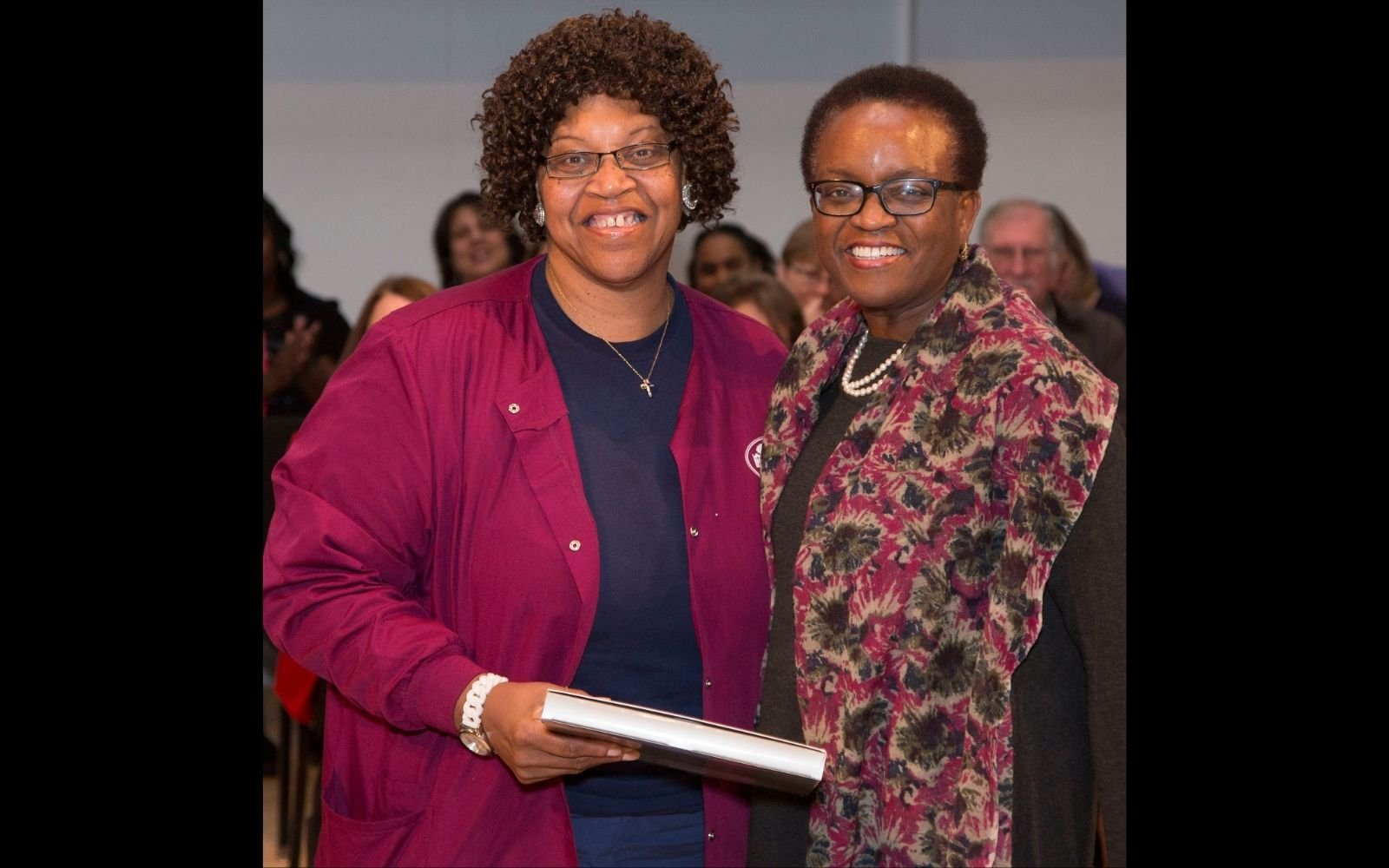 Two woman stand beside each other and embrace, smiling at the camera. The woman on the left wears a garnet jacket and navy top and has shoulder length hair. The woman on the right has close cropped hair and wears glasses and a long patterned jacket.