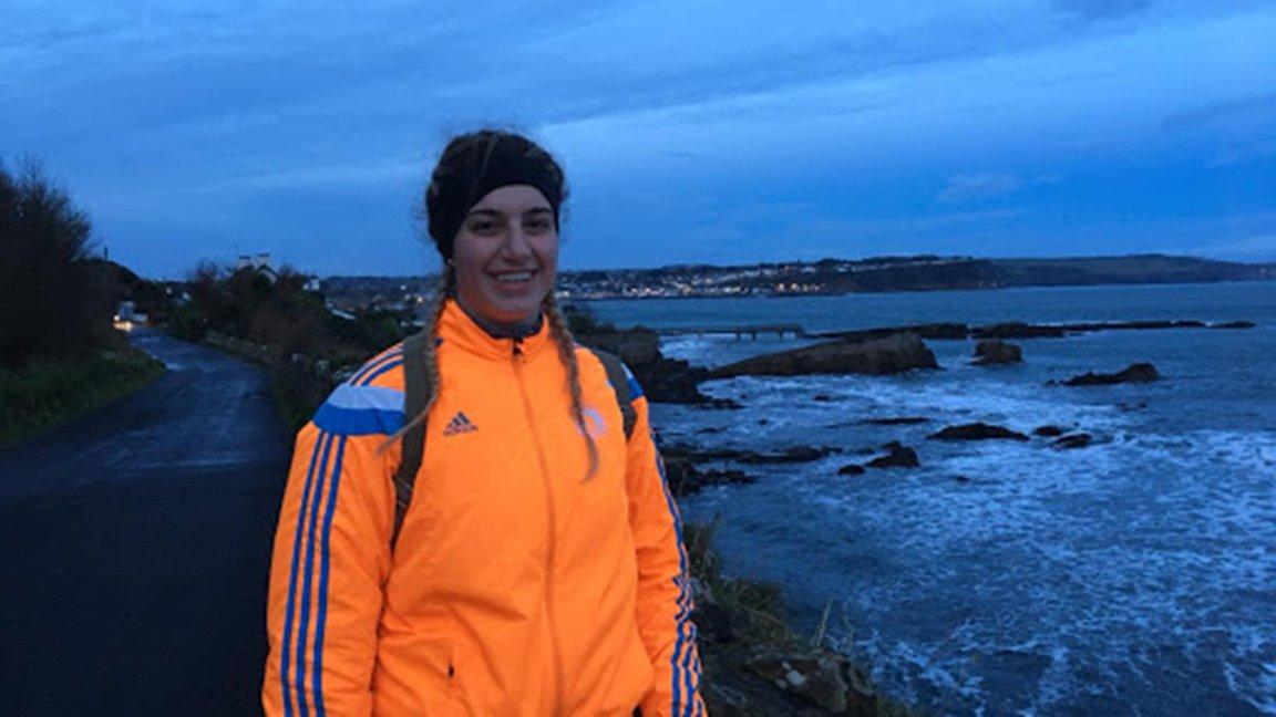 student in bright orange jacket near the sea