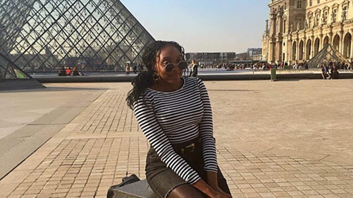 student in front of the Louvre