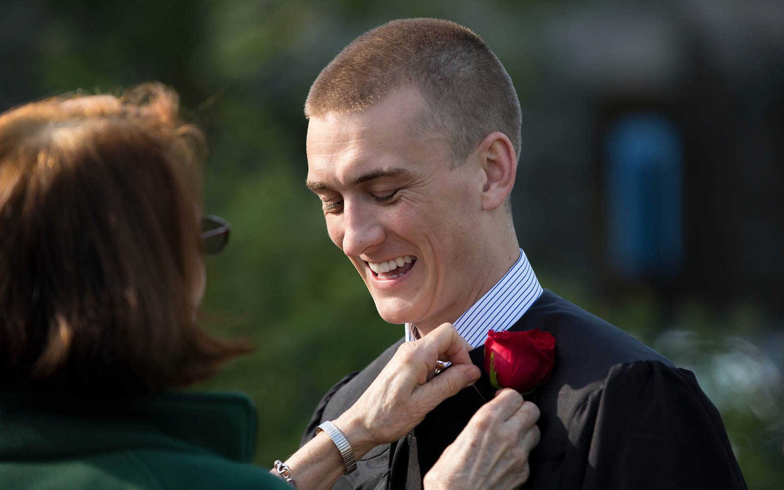 student getting rose attached to gown