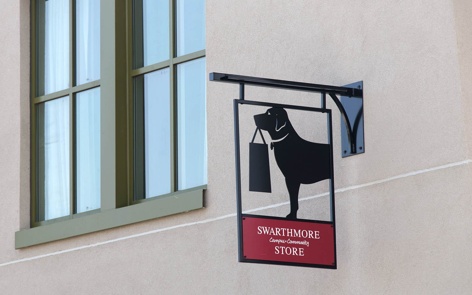 Bookstore sign of dog holding a bag in its mouth