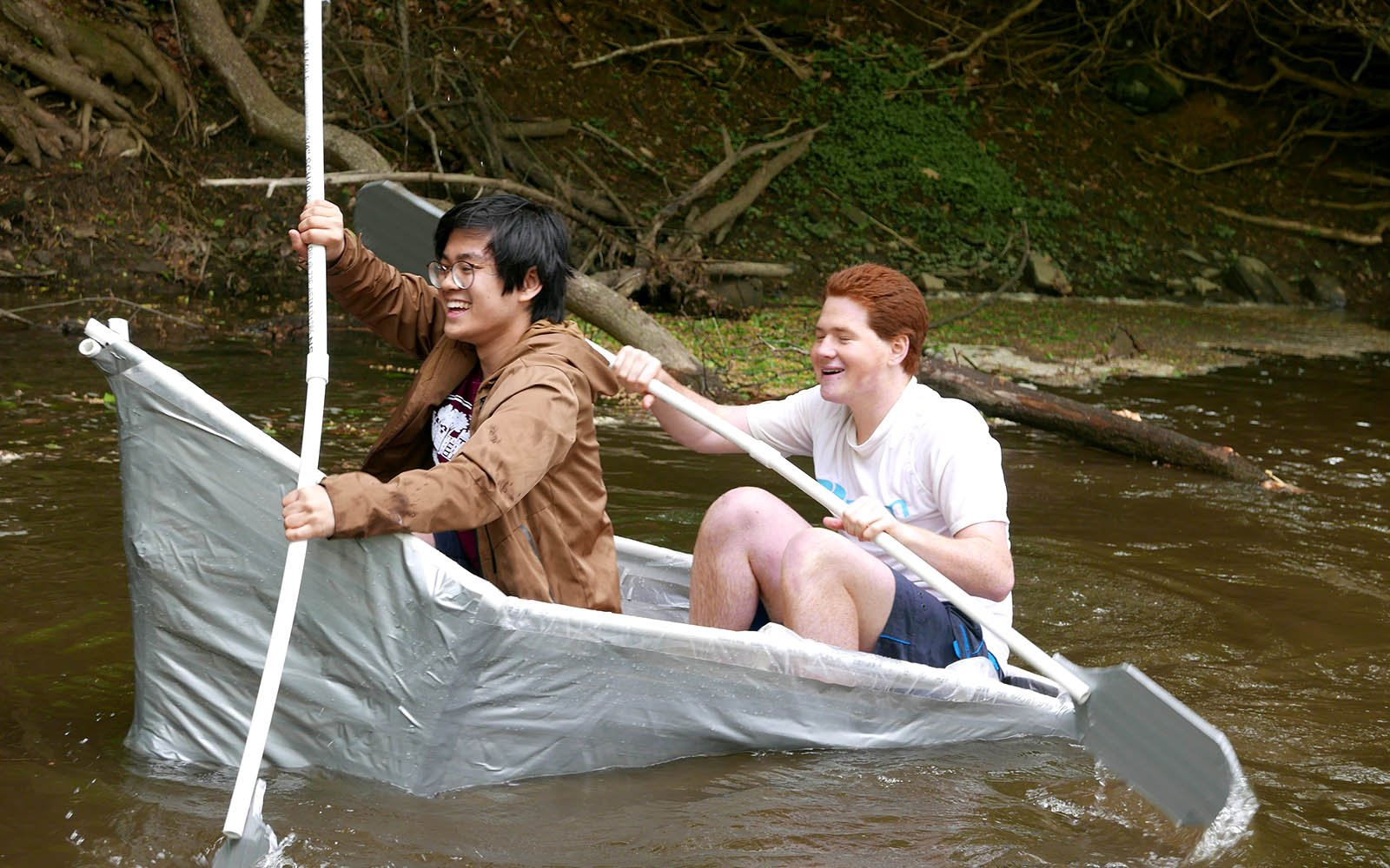 students paddling in the handmade boat