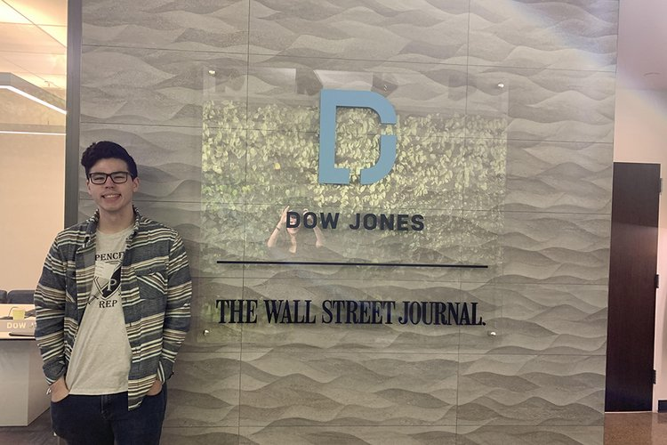 """Student stands in front of sign that reads """"Wall Street Journal"""""""
