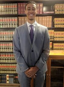 David Buckley on the first day day of work in the offices of the NAACP LDF, standing in front of various legal texts