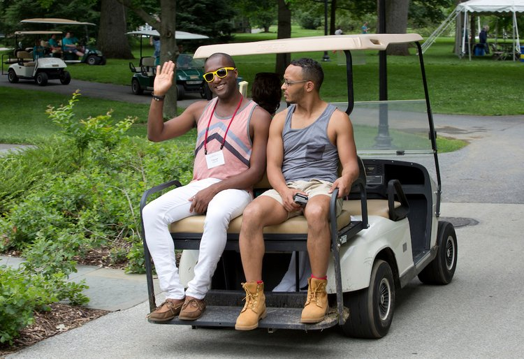 Young alumni catch a ride on a golf cart