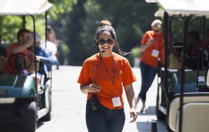 An Alumni Weekend student worker stand next to a golf cart