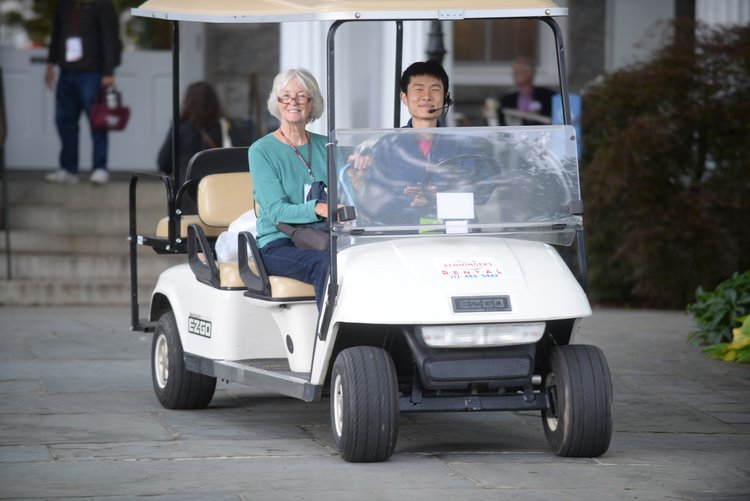 A student work and alumna on a golf cart
