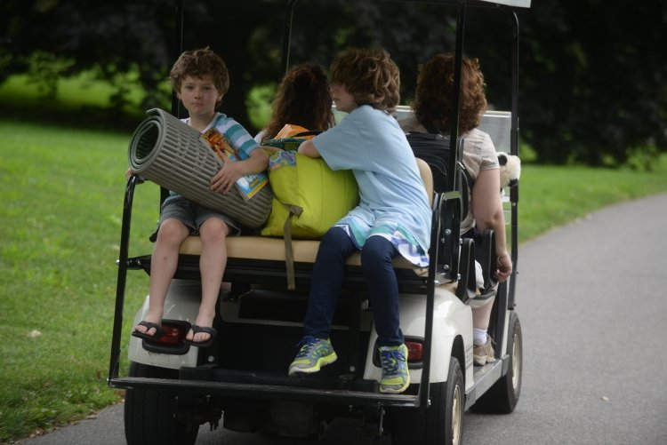 Visitors ride with their luggage on a golf cart