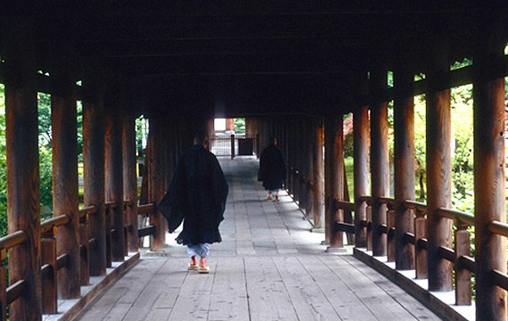 Monks walking through a covered bridge in a forested setting