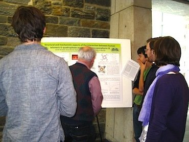 Faculty, students, and visitors gather around Jack Nicoludis and Steven Barrett's poster.