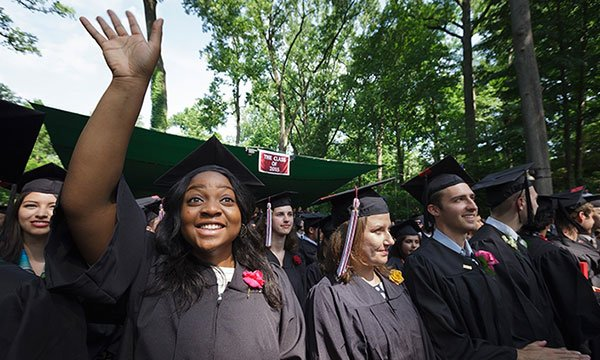 A graduate waves to her family