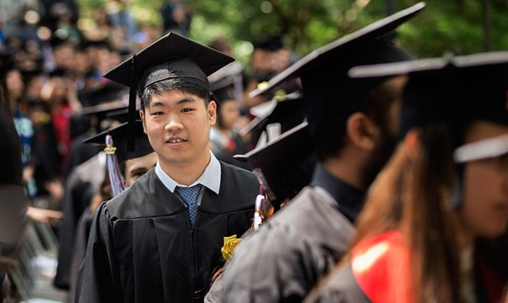 A student looks out from a line of graduates at Commencement