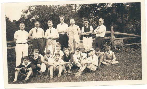 Photograph of a group of boys and men posing in front of a fence.