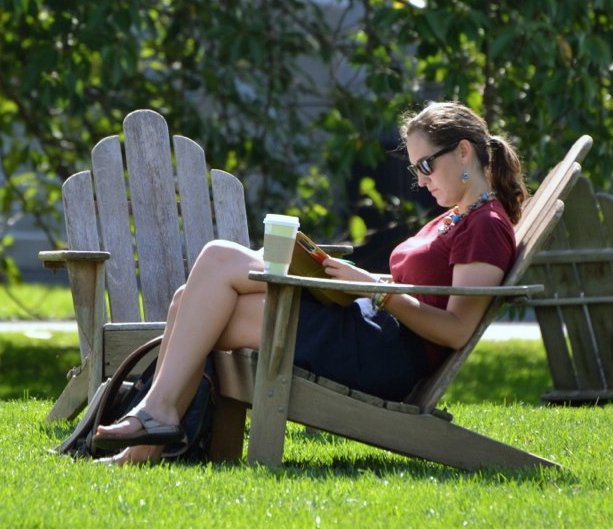 Student seated in an adirondack chair, reading outside in the sun