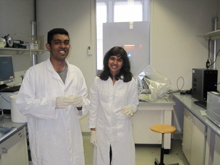 Navin and Michelle don lab coats before getting to work at the IECB, demonstarting both good lab safety and impeccable fashion