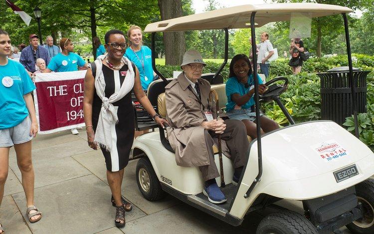 Student drives golf cart during alumni weekend