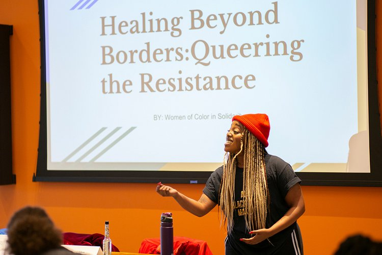 "Student in front of screen that says ""Healing Beyond Borders: Queering the Resistance"""