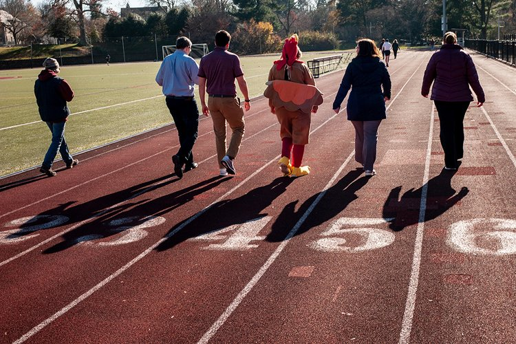 Community members walk around track for Turkey Trit