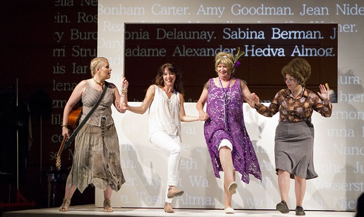 Four women on stage linking arms and dancing.