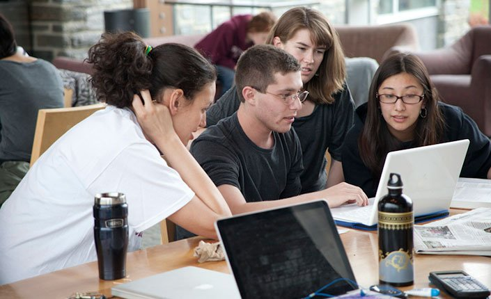 Students gather around a computer