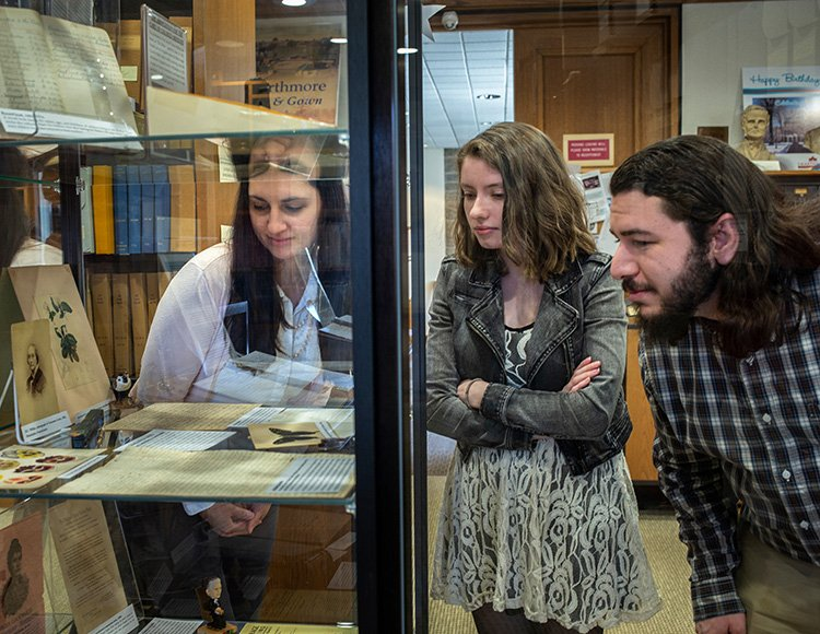 Library interns examine archival documents