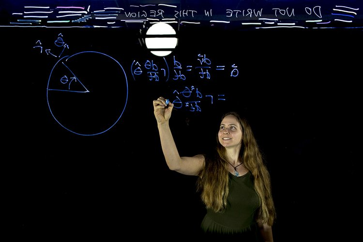 Woman writes equations on transparent chalkboard