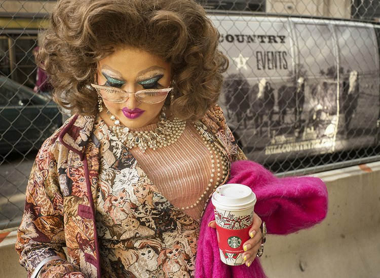 Drag queen stands in front of chain link fence
