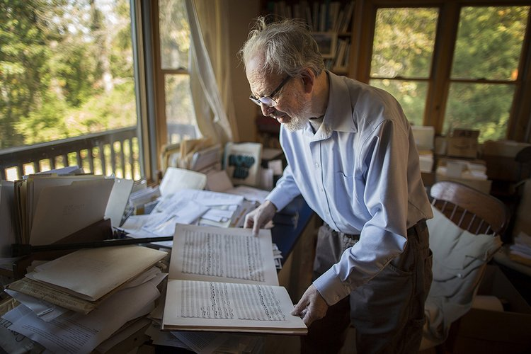 Man examines old sheet music in office